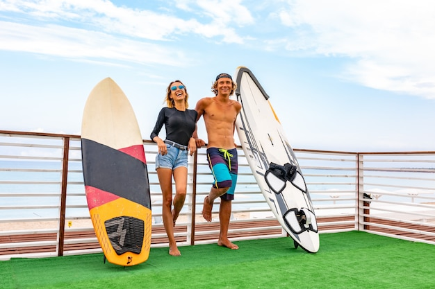 Smiling young active couple surfers relaxing on the beach after sport with surfboard. healthy lifestyle. extreme water sports Premium Photo