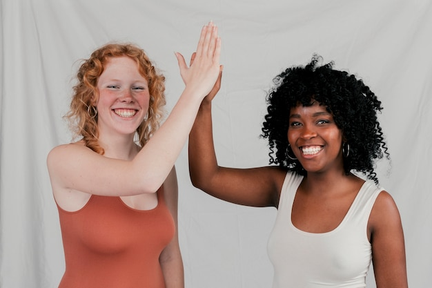 Smiling young african and blonde women giving high five against grey backdrop Free Photo