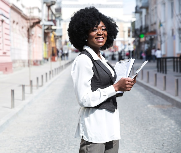 Smiling young african businesswoman standing in city road holding clipboard looking away Free Photo