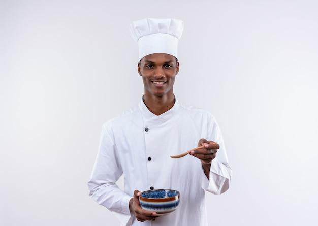 シェフの制服を着た笑顔の若いアフリカ系アメリカ人料理人は、コピースペースと孤立した白い背景の上のボウルを保持し、ポイントします 無料写真