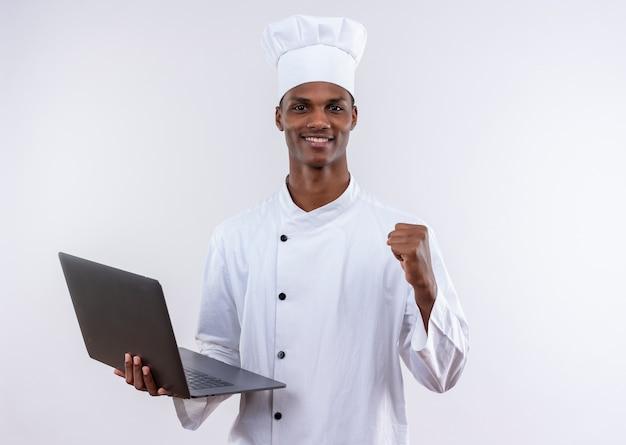 シェフの制服を着た笑顔の若いアフリカ系アメリカ人料理人はラップトップを保持し、コピースペースで孤立した白い背景に拳を維持します 無料写真