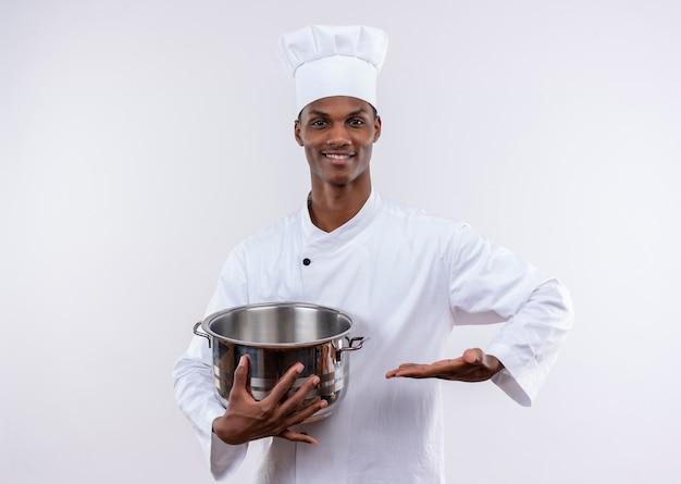 シェフの制服を着た笑顔の若いアフリカ系アメリカ人料理人は鍋を保持し、コピースペースで孤立した白い背景に手をまっすぐに保ちます 無料写真