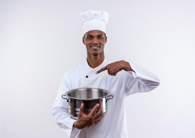シェフの制服を着た笑顔の若いアフリカ系アメリカ人料理人は、コピースペースと孤立した白い背景の上の鍋で鍋とポイントを保持します 無料写真