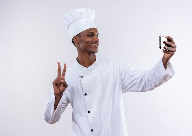 シェフの制服を着た若いアフリカ系アメリカ人料理人の笑顔は、コピースペースと孤立した白い背景の上の電話とジェスチャーの勝利のサインを見てください 無料写真