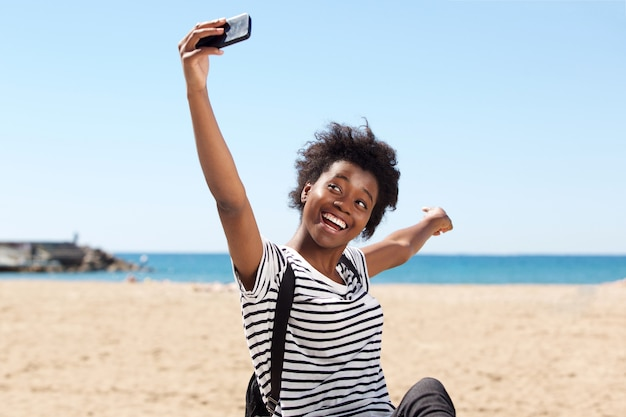 smiling young afro american female on the beach and talking selfie