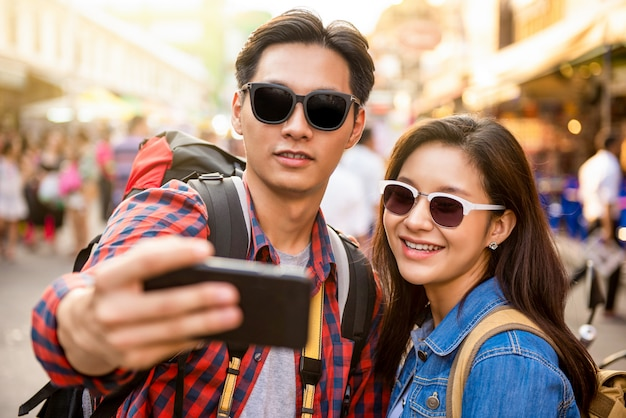 Smiling young asian couple tourists taking selfie while traveling in khao san road bangkok thailand during summer vacation Premium Photo