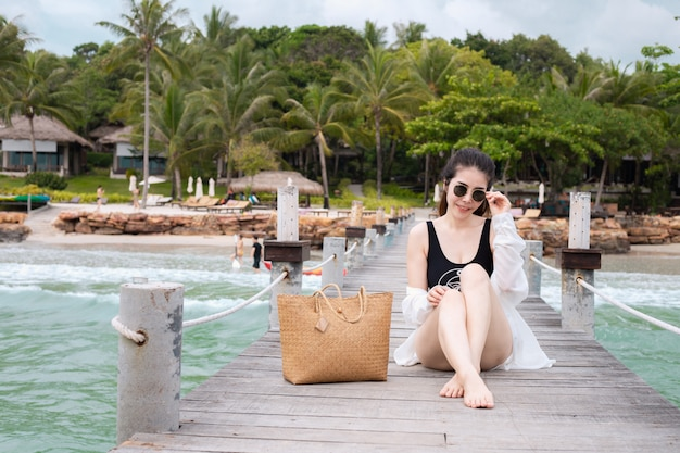 Smiling young asian woman in swimsuit sitting on wood bridge with sea background. summer holiday concept. Premium Photo
