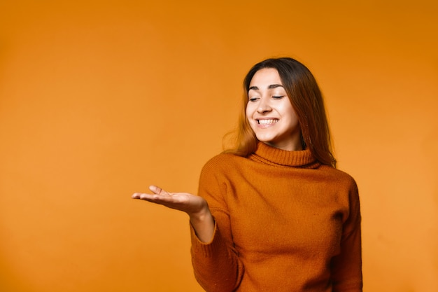 Smiling young attractive caucasian girl is dressed in pullover Free Photo
