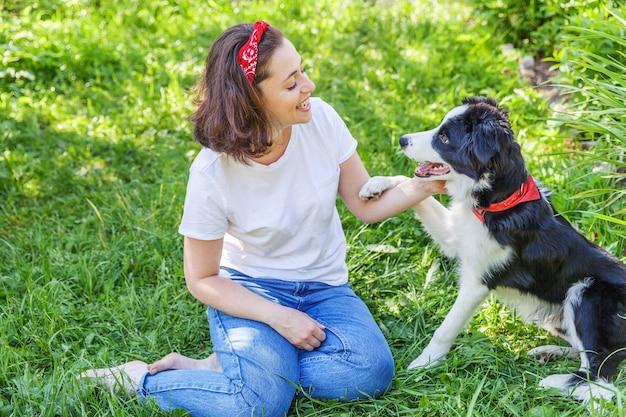 여름 정원에서 귀여운 강아지 보더 콜리와 놀고 웃는 젊은 매력적인 여자 프리미엄 사진