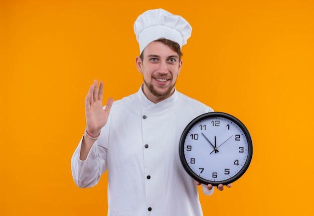 Un giovane uomo barbuto sorridente del cuoco unico in orologio da parete della tenuta dell'uniforme bianca mentre osserva su una parete arancione Foto Gratuite