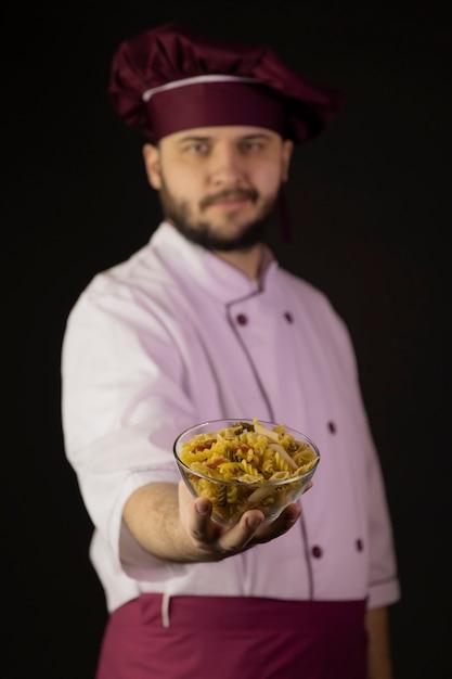Улыбающийся молодой бородатый шеф-повар в униформе держит миску с макаронами Premium Фотографии