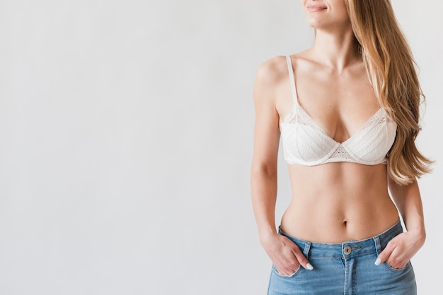 Smiling young blond woman posing in bra and jeans Free Photo