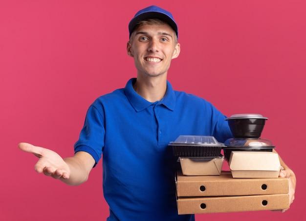 Il giovane ragazzo biondo sorridente delle consegne tiene la mano aperta e tiene i contenitori e i pacchetti dell'alimento sui contenitori di pizza isolati sulla parete rosa con lo spazio della copia Foto Gratuite