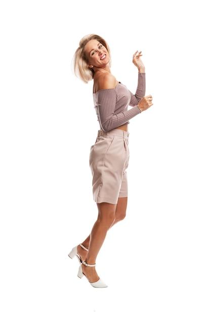 핑크 정장 점프에 웃는 젊은 금발의 여자. 흰 벽에 고립. 프리미엄 사진