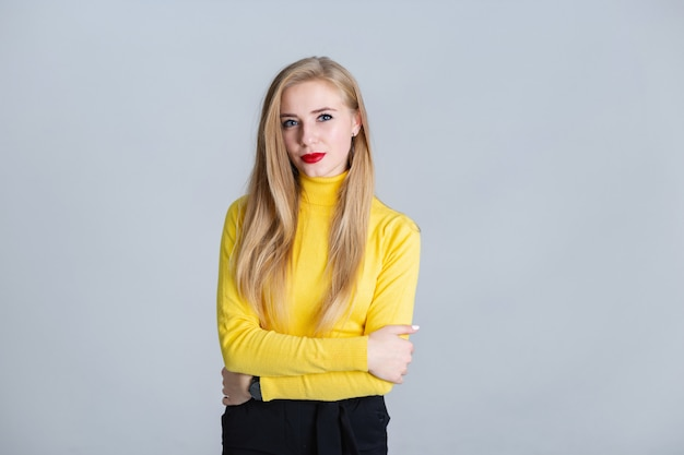 Smiling young blonder woman folded her hands Premium Photo