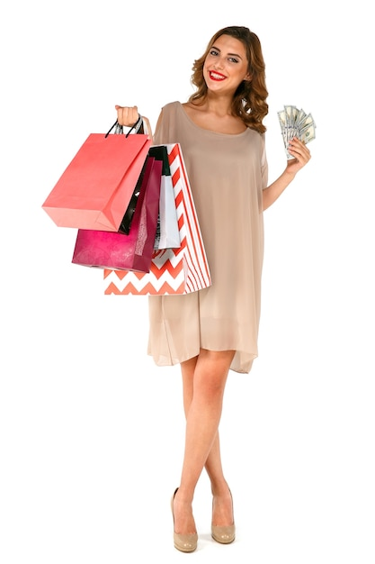 Smiling young brunette woman in dress holding money dollars, posing with shopping bags Free Photo