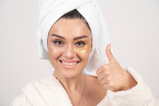 화장품 눈 패치 목욕 가운을 입고 웃는 젊은 갈색 머리 여자 무료 사진