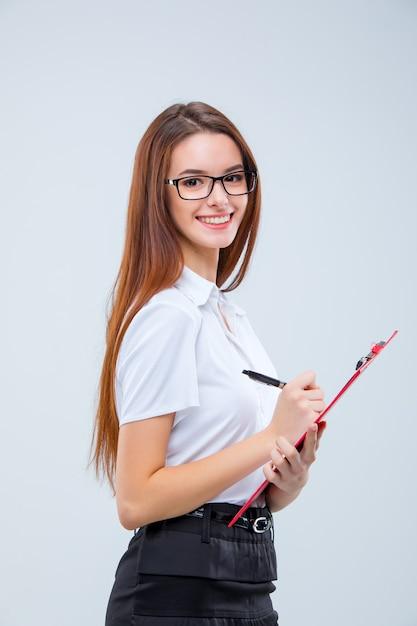 Улыбающаяся молодая деловая женщина в очках с ручкой и буфером обмена Бесплатные Фотографии