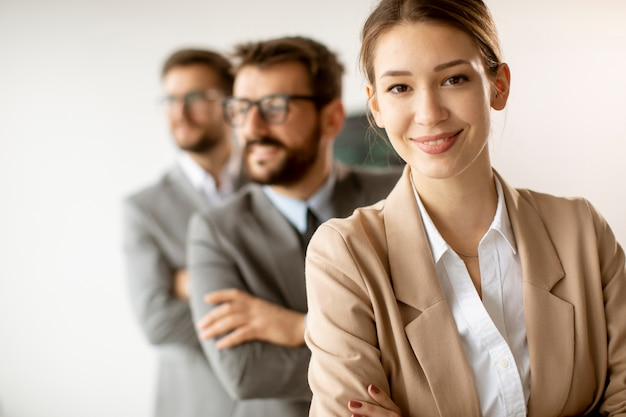Smiling young business woman standing with group of corporate colleagues in a row together at the office Premium Photo