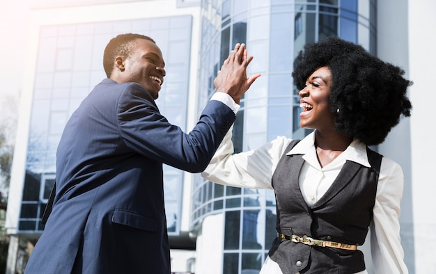 Smiling young businessman and businesswoman giving high five in front of corporate building Free Photo