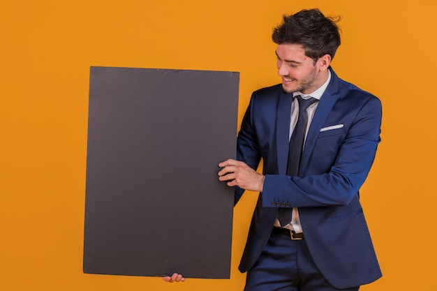 A smiling young businessman holding blank black placard against an orange backdrop Free Photo
