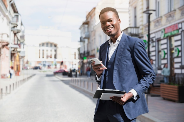 Smiling young businessman holding clipboard and mobile phone in hand standing on road in city Free Photo