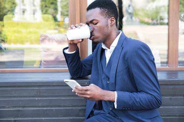 Smiling young businessman sitting on bench drinking the coffee Free Photo