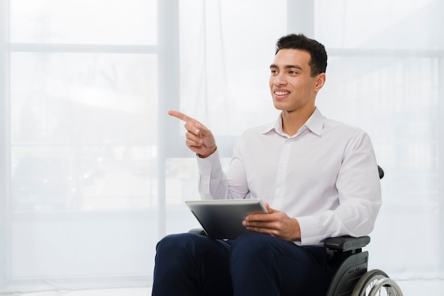 Smiling young businessman sitting on wheelchair holding digital tablet in hand pointing his finger to side Free Photo