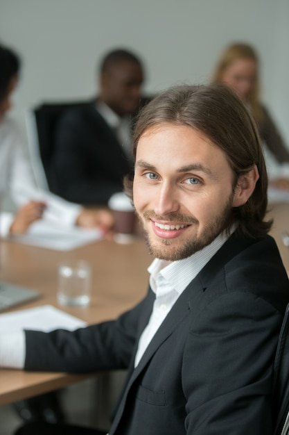 Smiling young businessman in suit looking at camera at meeting Free Photo