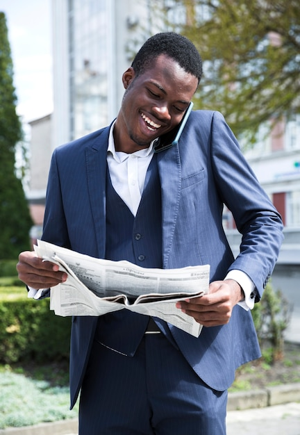 Smiling young businessman talking on mobile phone reading the newspaper Free Photo