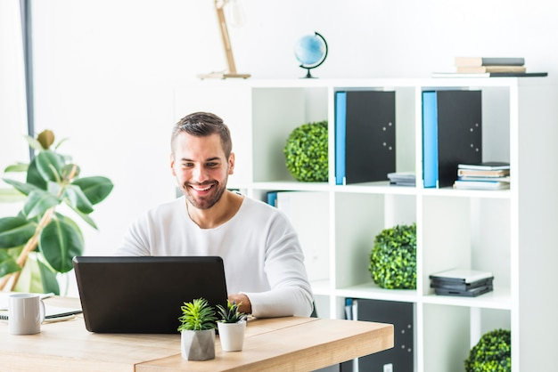 Smiling young businessman using laptop in office Free Photo