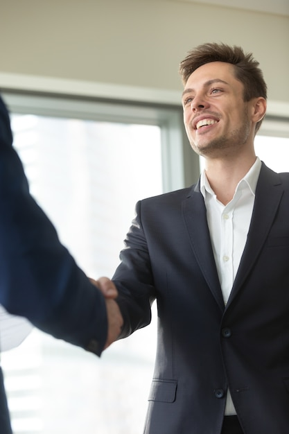Smiling young businessman wearing black suit shaking male hand, Free Photo