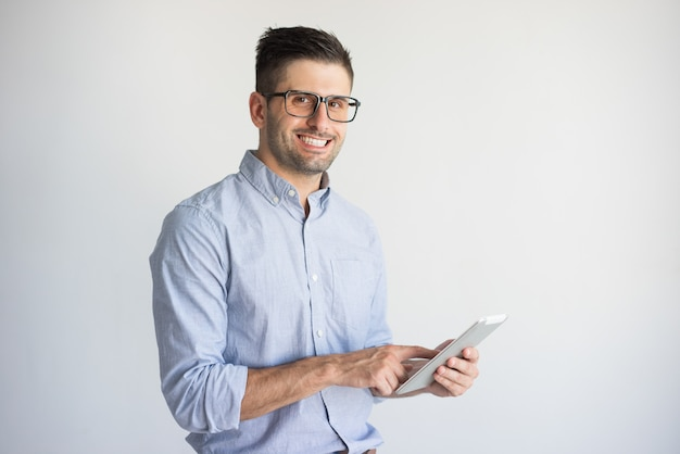 Smiling young businessman wearing glasses using digital tablet. Free Photo