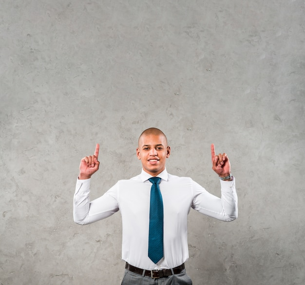 Smiling young businessman with his arms raised pointing his finger upward against grey wall Free Photo