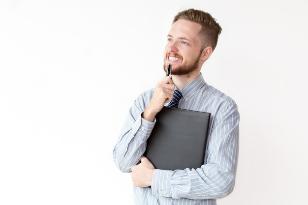 Smiling young businessman with pensive expression Free Photo