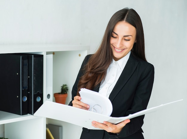 Smiling young businesswoman looking at the documents in the whit folder Free Photo