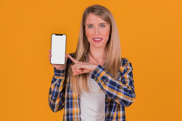 Smiling young businesswoman pointing his finger at mobile phone against an orange background Free Photo