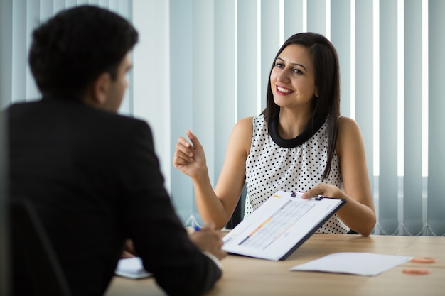 Smiling young businesswoman showing contract to partner Free Photo