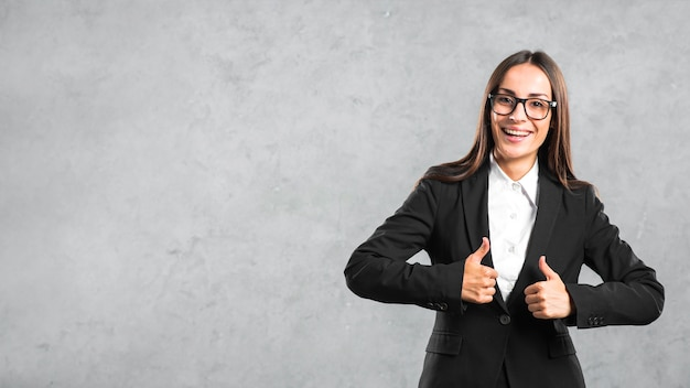 Smiling young businesswoman showing thumb up sign against gray backdrop Free Photo