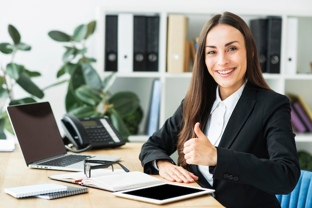 Smiling young businesswoman sitting at workplace showing thumb up sign Free Photo