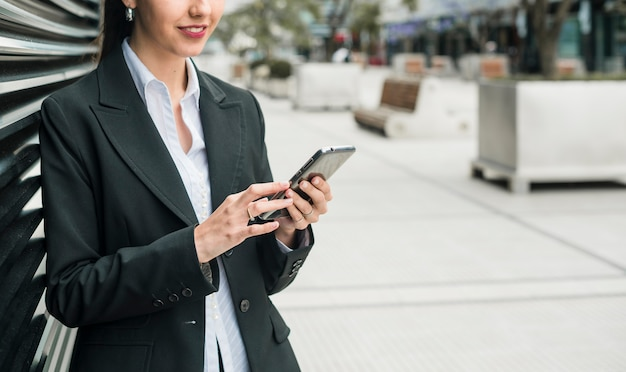 Smiling young businesswoman using smart phone Free Photo