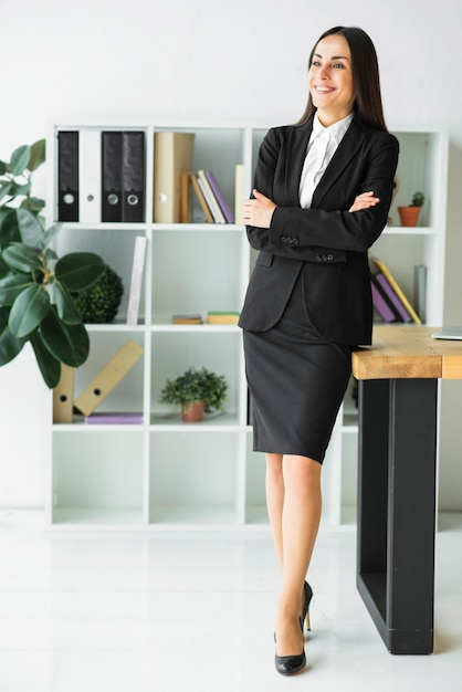 Smiling young businesswoman with her arms crossed looking away Free Photo