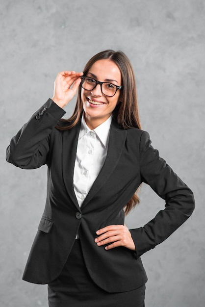 Smiling young businesswoman with her hand on hip standing in front of grey wall Free Photo