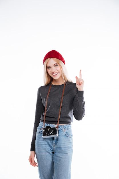 Улыбающийся молодой случайные молодая женщина, указывая пальцем вверх Бесплатные Фотографии