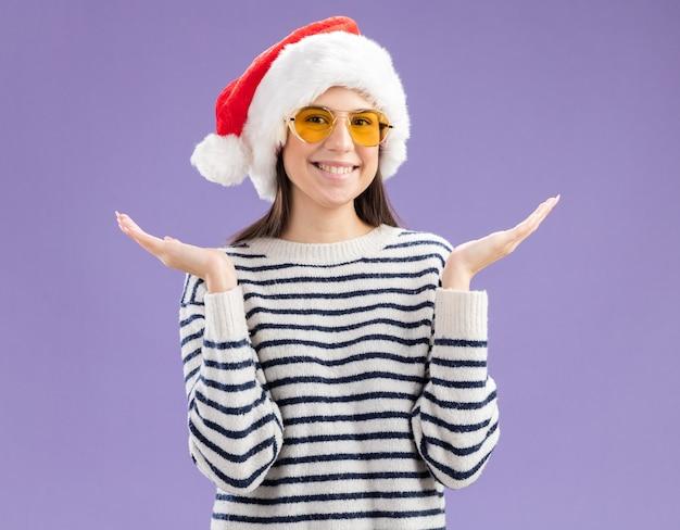 手を開いているサンタの帽子とサングラスで笑顔の若い白人の女の子 無料写真