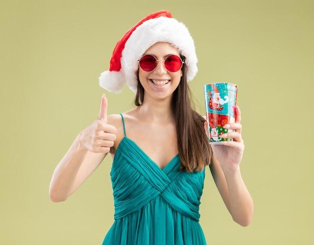 サンタの帽子とサングラスで笑顔の若い白人の女の子は紙コップと親指を持ち上げます 無料写真