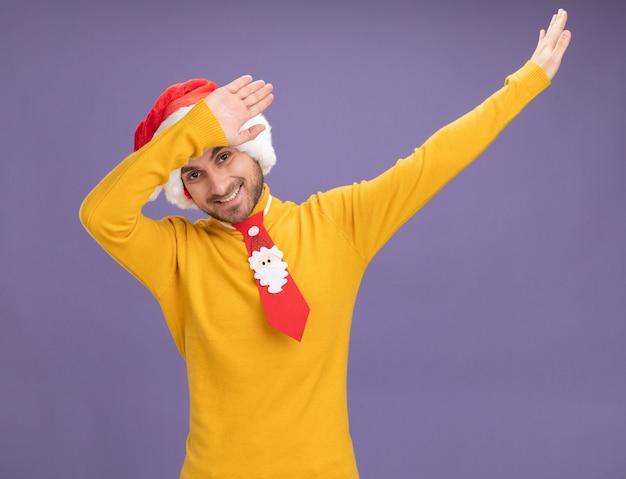 クリスマスの帽子とネクタイを身に着けている若い白人男性が紫色の背景で隔離の軽くたたくジェスチャーをしているカメラを見て笑っている 無料写真