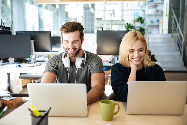 オフィスのコワーキングに座っている笑顔の若い同僚 無料写真