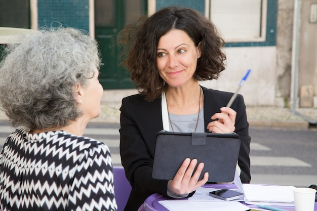 Smiling young consultant offering pen to elderly client Free Photo