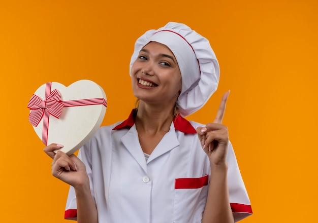 ハートの形を保持しているシェフの制服を着て笑顔の若い料理人女性は、孤立したオレンジ色の背景の上のボックスに指を指 無料写真
